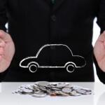 אדם שומר על תמונה של רכב ומטבעות על השולחן