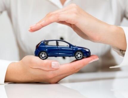 אשה מחזיקה דגם של רכב בין הידיים