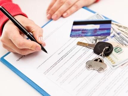 אשה חותמת על מסמך של ביטוח מקיף לרכב