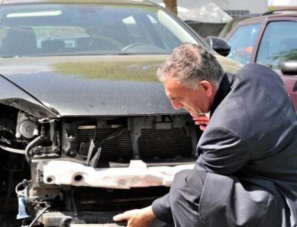 אדם יושב ליד רכב שנפגע בתאונת דרכים
